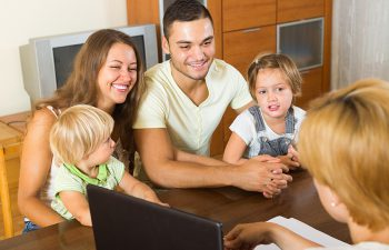 Positive young parents and two daughters sitting in front of social worker at home
